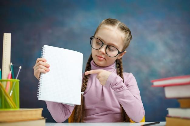 A menina consideravelmente caucasiano da escola primária aprende a foto