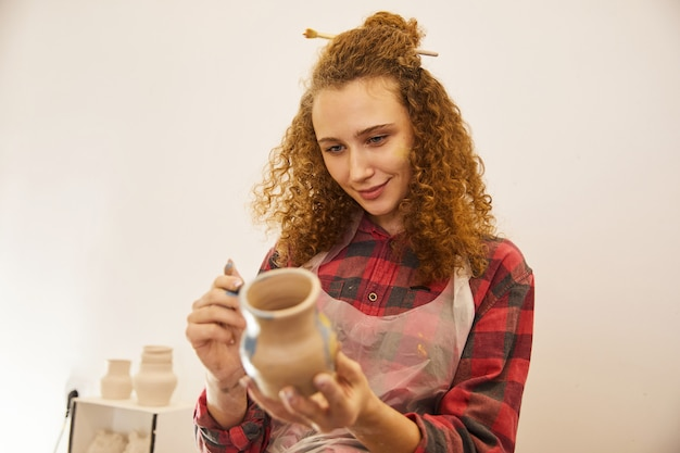A menina consideravelmente encaracolado pinta um vaso antes de cozer