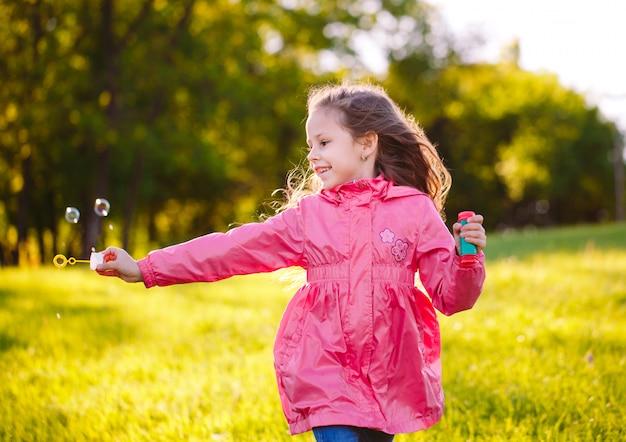 A menina corre e brinca com bolhas de sabão.