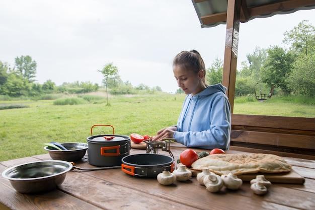 A menina corta tomates em uma placa de madeira no acampamento