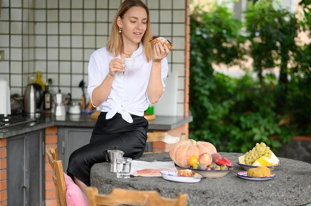 A menina cozinhou o café da manhã e bebe o café com sobremesa