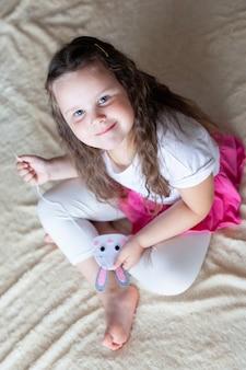 A menina criança costura um brinquedo de feltro sentado na cama sobre um cobertor bege; bordado