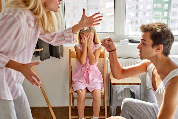 A menina criança está sofrendo de brigas entre os pais na família em casa, mulher e homem discutem na presença da filha