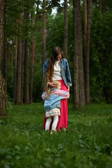 A menina criança feliz abraça a mãe de pé na grama do parque