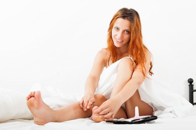 A menina cuida das unhas dos pés com uma tesoura na cama
