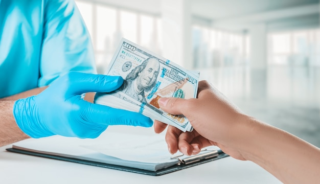 A menina dá ao médico um pacote de notas de cem dólares