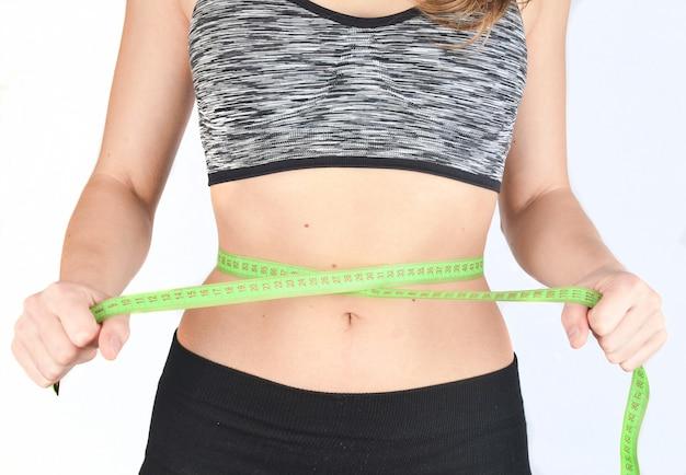 A menina da aptidão nos esportes cobre a cintura da régua de medição no fundo branco. o conceito de perda de peso.