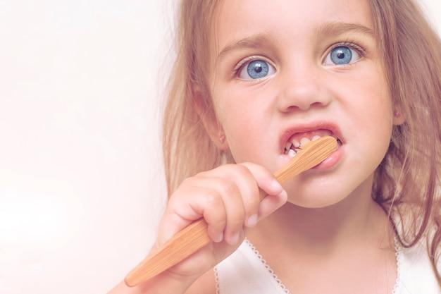 A menina da criança 3 anos velha escova seus dentes com uma escova de dentes de bambu. uma criança linda com grandes olhos azuis salva o planeta de plástico.