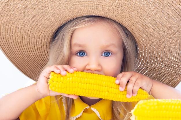 A menina da criança em um chapéu de palha na roupa amarela come o milho, foto do verão. sobre um fundo claro