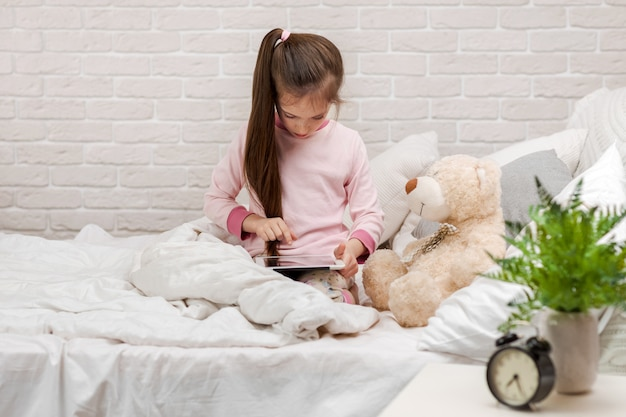 A menina da criança pequena encontra-se na cama usa a tabuleta digital.