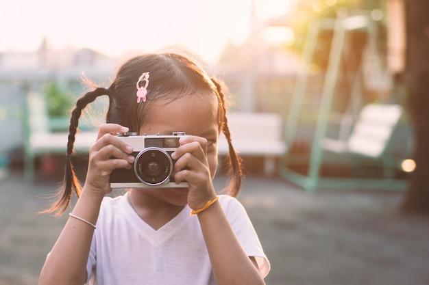 A menina da criança pequena toma a câmera do filme com feliz, estilo do vintage.