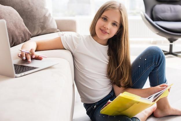A menina da escola estuda com laptop e livro em casa