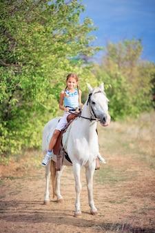 A menina da escola monta um pônei branco. uma criança montando um cavalo