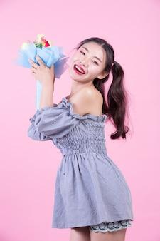 A menina da forma veste-se acima com gestos de mão em um fundo cor-de-rosa.