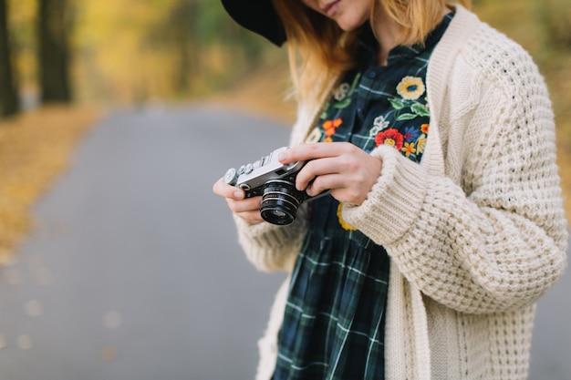 A menina da hippie com a câmera velha em uma camiseta e em um chapéu feitos malha anda parque do outono.