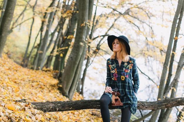 A menina da hippie com câmera velha em um chapéu anda parque do outono.