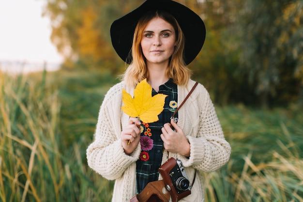 A menina da hippie com uma folha de bordo amarela em uma camiseta e em um chapéu feitos malha anda parque do outono.