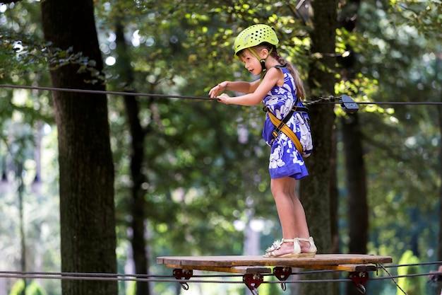 A menina da jovem criança no chicote de fios e no capacete de segurança uniu com a carabina ao cabo na maneira da corda no parque.