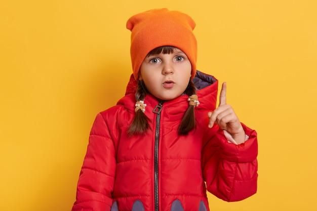 A menina da pré-escola mostra o dedo indicador isolado sobre a parede amarela, tem uma ótima ideia, tem uma aparência atenciosa, vestindo jaqueta vermelha e boné laranja