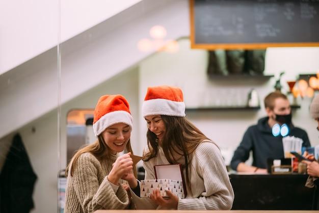 A menina dá um presente para sua amiga em caffe