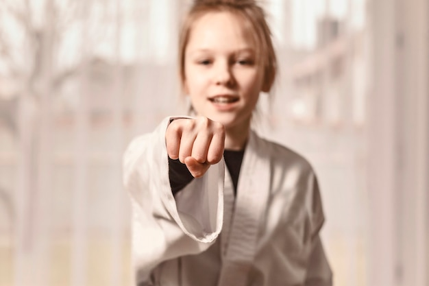 A menina dá um soco na mão dela e olha para a câmera