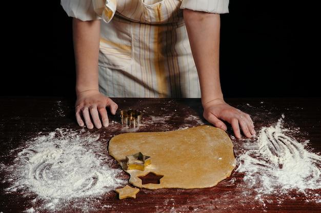 A menina de avental corta massa em forma de biscoitos em forma de estrelas em uma mesa de madeira
