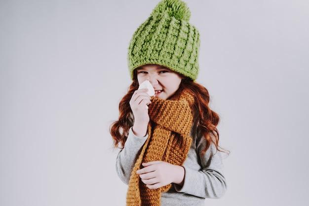 A menina de cabelo vermelha com lenço limpa o ranho com o guardanapo.