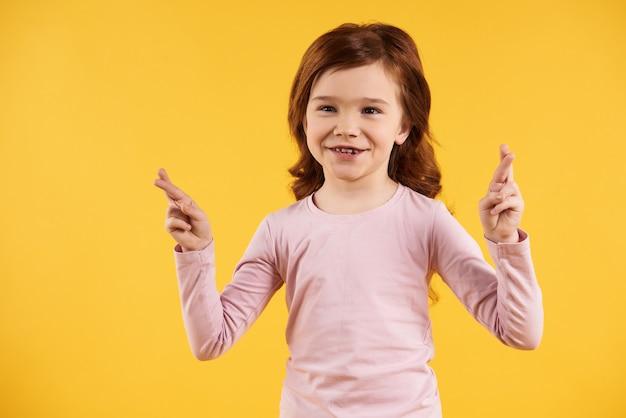 A menina de cabelo vermelha cruzou os dedos. conceito de superstição