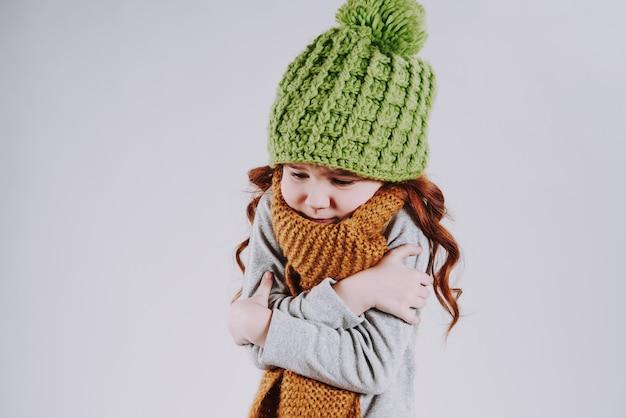 A menina de cabelo vermelha no tampão e no lenço da malha tenta aquecer-se.
