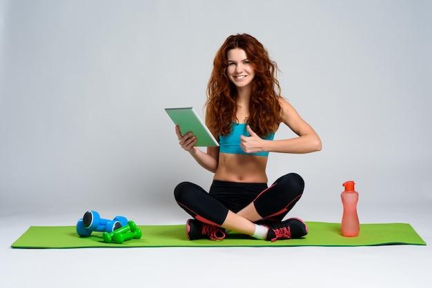 A menina de cabelo vermelha senta-se com a tabuleta no tapete do gym.