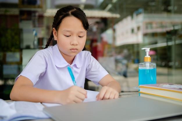 A menina de escola primária júnior faz lição de casa