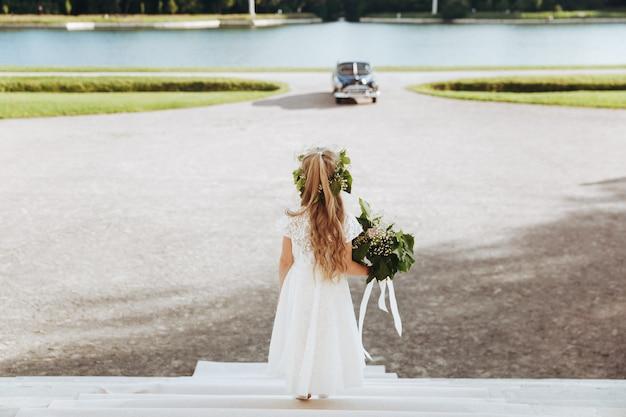 A menina de flor pequena olha o carro retro preto que monta para a casa