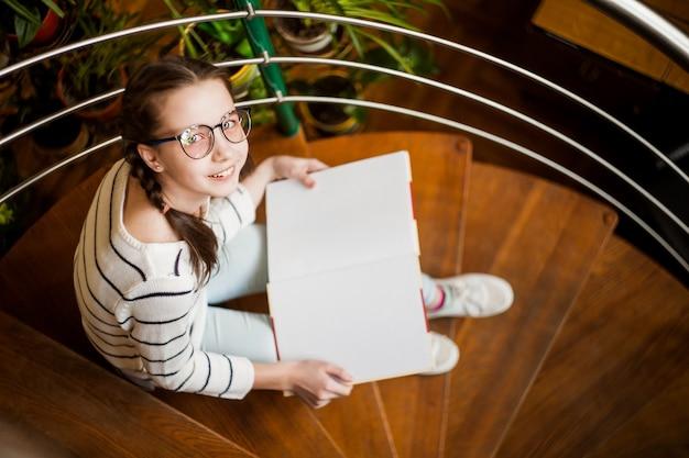 A menina de óculos com um livro nas mãos