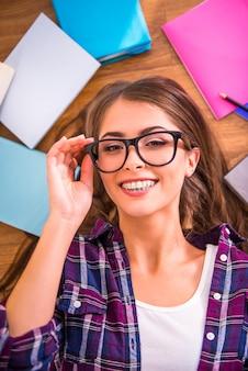 A menina de óculos encontra-se no chão e sorri.