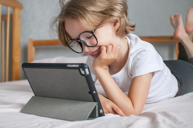 A menina de óculos faz o dever de casa online, deitada na cama em casa, comunicando-se com parentes