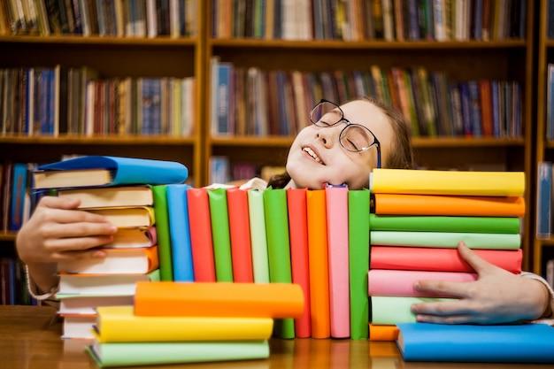 A menina de óculos na biblioteca abraça livros