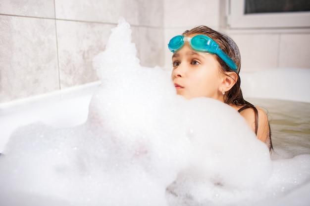 A menina de olhos azuis bonita em óculos de natação banha-se em um banho de espuma.