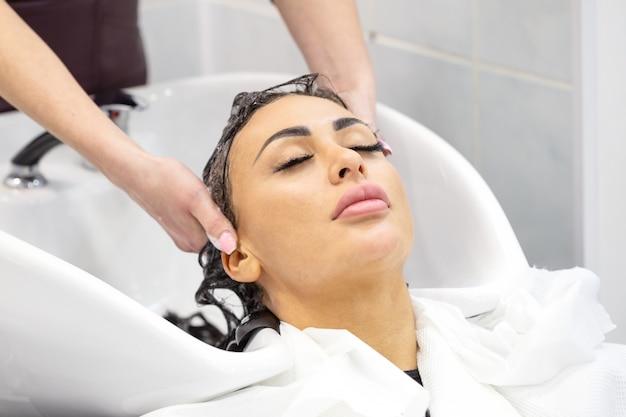 A menina de olhos fechados lava o cabelo em um salão de beleza