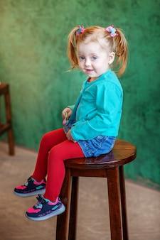 A menina de short sentado em uma cadeira.