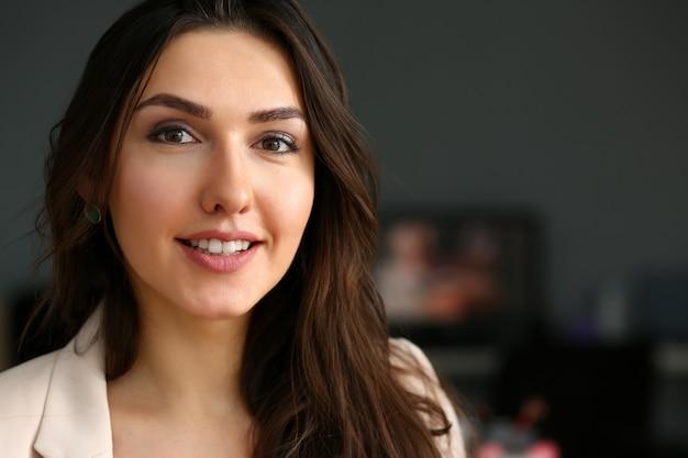 A menina de sorriso bonita no local de trabalho olha na câmera