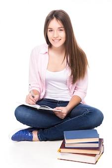 A menina de sorriso com livros está sentando-se no assoalho.
