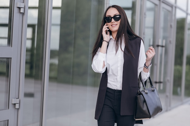 A menina de sorriso com óculos de sol e uma bolsa falando em seu telefone