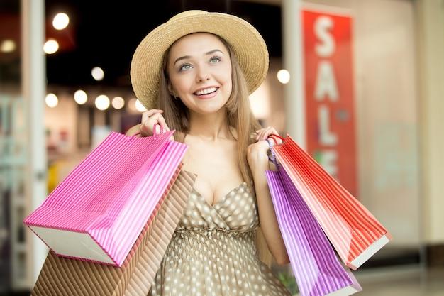 A menina de sorriso com um chapéu de palha e sacos de compras