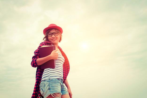 A menina de sorriso com um livro e chapéu vermelho