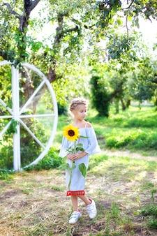 A menina de sorriso com uma trança em sua cabeça guarda o girassol no jardim. criança com girassol.