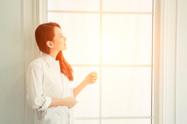 A menina de sorriso em uma janela