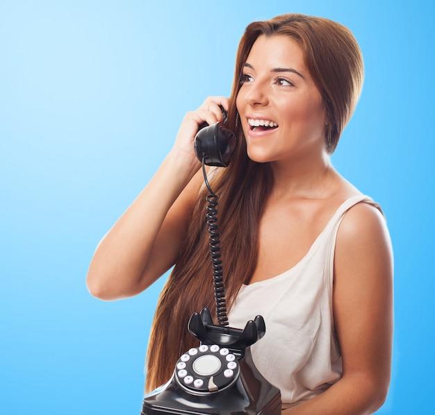 A menina de sorriso fala sobre o telefone à moda antiga