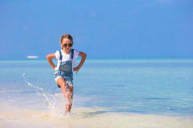 A menina de sorriso feliz adorável tem o divertimento em férias da praia