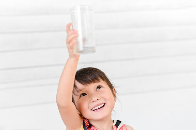 A menina de sorriso levantou um copo de leite que foi todo o leite consumido em cima na parede branca da casa, menina bebendo leite e deixando um bigode