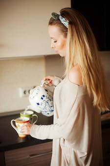 A menina de sorriso na cozinha derrama o chá na manhã